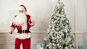 Santa Claus che fa danza moderna accanto all'albero di Natale stock footage