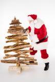 Santa Claus che fa l'albero di Natale Immagine Stock
