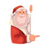 Santa Claus che guarda da dietro la parete e che mostra qualcosa Fotografie Stock Libere da Diritti