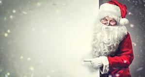 Santa Claus che indica sul fondo in bianco dell'insegna della pubblicità con lo spazio della copia Immagini Stock Libere da Diritti