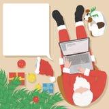 Santa Claus che lavora al computer portatile a casa vicino all'albero di Natale Fotografia Stock