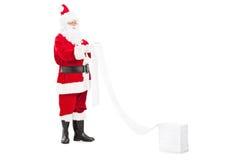 Santa Claus che legge una lista dei desideri Immagine Stock