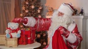 Santa Claus che mette i regali nella borsa isolata vicino al archivi video