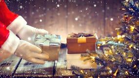 Santa Claus che mette il contenitore di regalo sotto l'albero di Natale Fotografie Stock Libere da Diritti