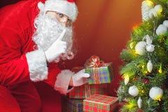 Santa Claus che mette il contenitore o il presente di regalo sotto l'albero di Natale Fotografia Stock Libera da Diritti
