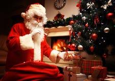 Santa Claus che mette il contenitore o il presente di regalo sotto l'albero di Natale alla notte di vigilia it è un segreto Non d Immagine Stock