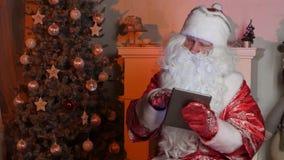 Santa Claus che per mezzo del computer della compressa per praticare il surfing Internet stock footage