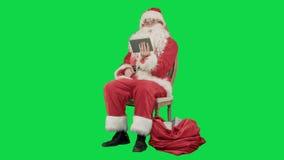 Santa Claus che per mezzo del computer della compressa per praticare il surfing Internet video d archivio