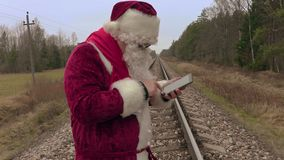 Santa Claus che per mezzo del PC della tavola sulla ferrovia archivi video