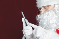 Santa Claus che per mezzo di un telefono cellulare al tempo di Natale Fotografia Stock