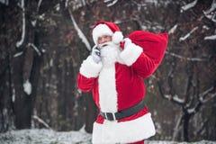 Santa Claus che porta grande sacco Fotografie Stock