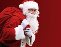 Santa Claus che porta sacco rosso enorme con i presente Immagine Stock