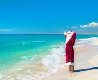 Santa Claus che si rilassa alla spiaggia del mare - concetto di Natale Fotografia Stock Libera da Diritti