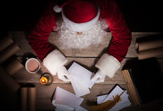 Santa Claus che si siede alla tavola nella sua stanza ed alla lettera d'apertura di Natale dal bambino fotografie stock
