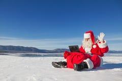 Santa Claus che si siede sulla neve, esaminante le notizie del computer portatile Immagine Stock