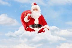 Santa Claus che si siede sulle nuvole con la borsa e la volata Fotografia Stock Libera da Diritti