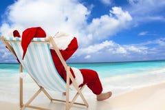 Santa Claus che si siede sulle sedie di spiaggia Concetto di festa di Natale Immagine Stock