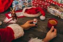 Santa Claus che tiene una palla di vetro di Natale Fotografie Stock