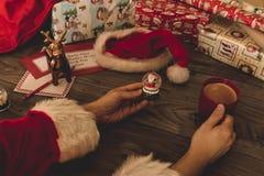 Santa Claus che tiene una palla di vetro di Natale alla sua tavola di legno con i regali Fotografia Stock