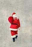 Santa Claus che va con una borsa dei regali Immagini Stock Libere da Diritti
