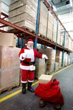 Santa claus checking list of gifts in storehouse stock images