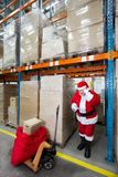 Santa claus checking list of gifts in storehouse Royalty Free Stock Image
