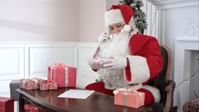 Santa Claus checking presents and making notes in the list of children`s wishes. Professional shot on BMCC RAW with high dynamic range. You can use it e.g. in Royalty Free Stock Photos