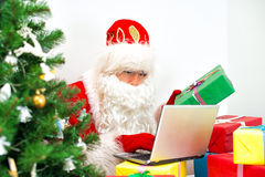 Santa Claus checking wish list. Stock Photos