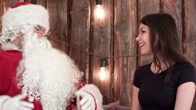 Santa Claus cheerfully talking to a pretty young brunette in black dress stock footage