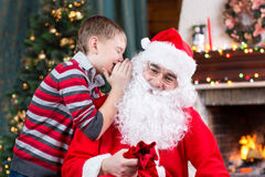Santa Claus and child boy. Kid telling his Stock Photography