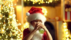 Santa Claus child holding Christmas cookies and milk against Christmas tree background. Christmas cookies and milk. Thanksgiving day and Christmas stock video footage