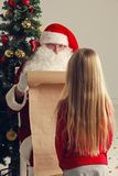 Santa Claus and child. Santa Claus with with list or nice or naugthy list paper with small girl near christmas tree Stock Photography