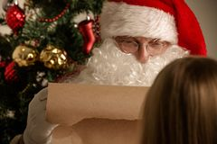 Santa Claus and child. Santa Claus with with list or nice or naugthy list paper with small boy near christmas tree Royalty Free Stock Photo