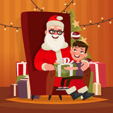 Santa Claus with a child sitting in a chair. Stock Photo