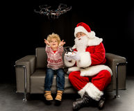 Santa Claus with child using hexacopter drone. And sitting on sofa royalty free stock image