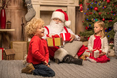 Santa Claus and children with Christmas gifts. Happy Santa Claus and children sitting on carpet with Christmas gifts Royalty Free Stock Image