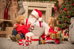 Santa Claus and children with Christmas gifts. Happy Santa Claus and children sitting on carpet with Christmas gifts Royalty Free Stock Photos