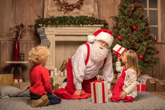 Santa Claus and children with Christmas gifts. Happy Santa Claus and children sitting on carpet with Christmas gifts Royalty Free Stock Images