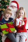 Santa Claus and children. With christmas gifts near christmas tree Royalty Free Stock Image