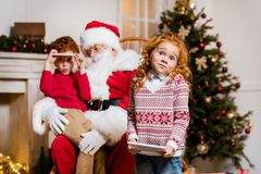 Santa claus and children with digital devices. Portrait of santa claus in rolling chair and children with digital devices Stock Photos