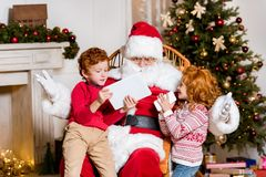 Santa claus and children with digital devices. Portrait of santa claus in rolling chair and children with digital devices Stock Photography