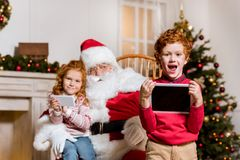 Santa claus and children with digital devices. Portrait of santa claus in rolling chair and children with digital devices Royalty Free Stock Photos
