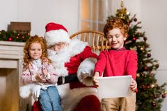 Santa claus and children with digital devices. Portrait of santa claus in rolling chair and children with digital devices Royalty Free Stock Image