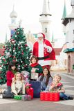 Santa Claus And Children With Gifts By Christmas Royalty Free Stock Image