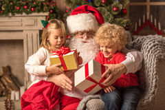 Santa Claus with children holding gift boxes Stock Images