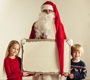 Santa Claus and children. Santa Claus with children holding vintage paper billboard with copy space for text Royalty Free Stock Photos