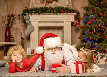 Santa Claus and children lying on carpet. Happy Santa Claus and children lying on carpet with Christmas gifts Royalty Free Stock Images