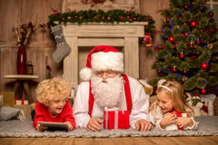 Santa Claus and children lying on carpet Royalty Free Stock Photography