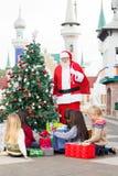 Santa Claus With Children Opening Presents cerca Imágenes de archivo libres de regalías