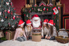 Santa Claus and children opening presents at fireplace. Kids and father in Santa costume and beard open Christmas gifts Stock Photography